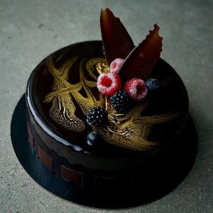 Schokobraune Spiegelglasur mit Beeren und Schokodekor
